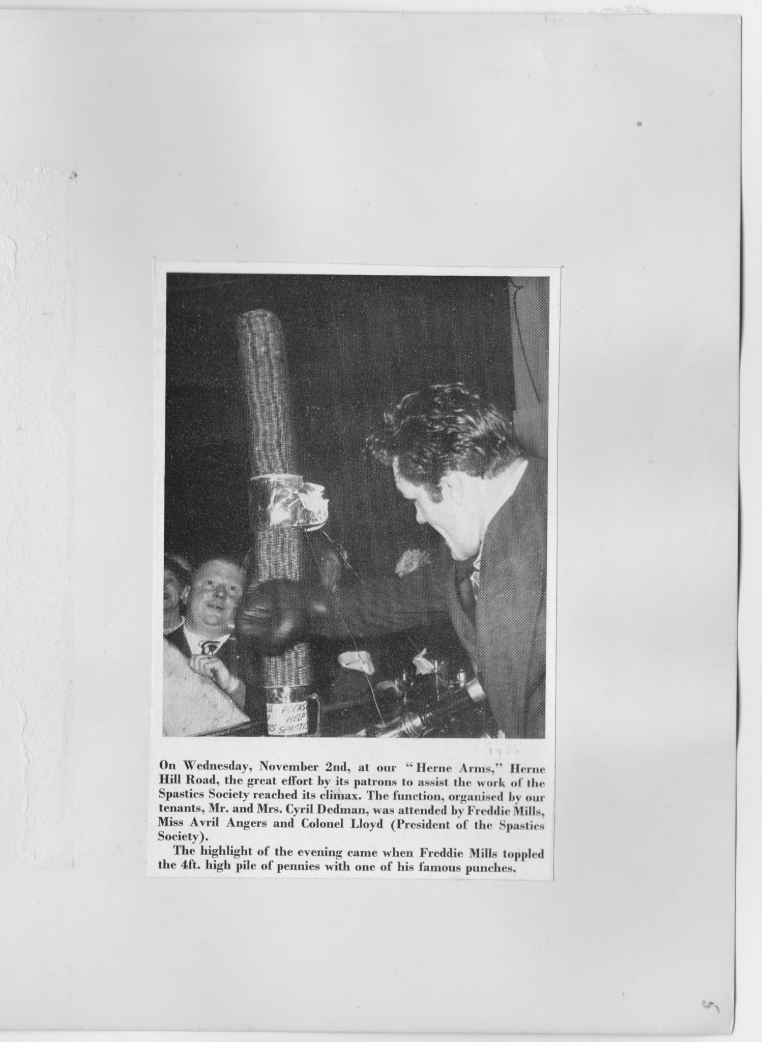 Boxer Freddie Mills knocks over a pile of pennies at the Herne Arms circa 1956